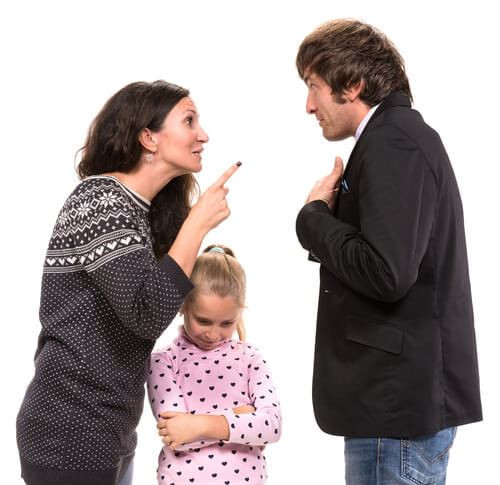 Sad daughter standing between her parents as they argue